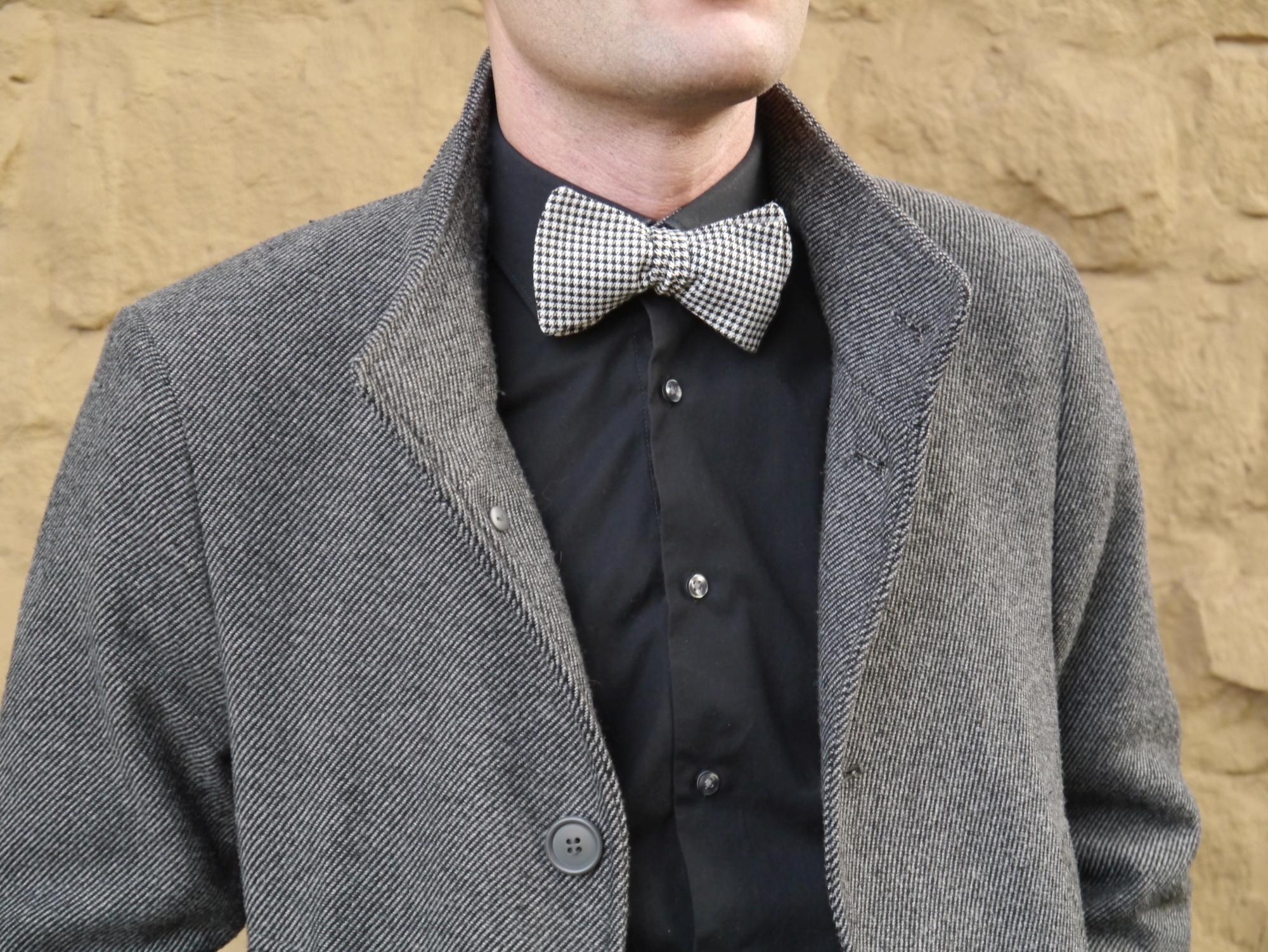 schwarz weiß karierte fliege zum selberbinden auf schwarzes hemd und mantel
