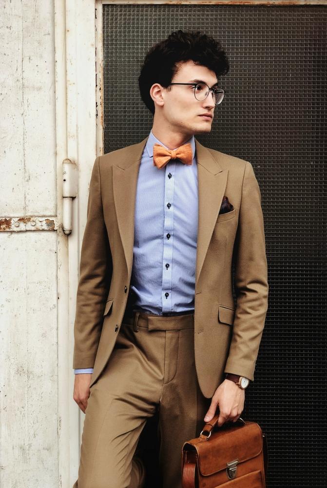 orangene fliege auf blaues hemd und brauner anzug einstecktuch