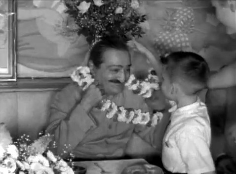 Meher Baba being garlanded by Larry Karrasch at Longchamps Restaurant, New York City, 22nd July 1956