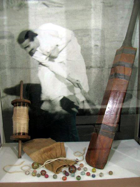 Display case at the museum at Meherabad showing Meher Baba's cricket bat, marbles and kite string - courtesy of Jessica Mednick.