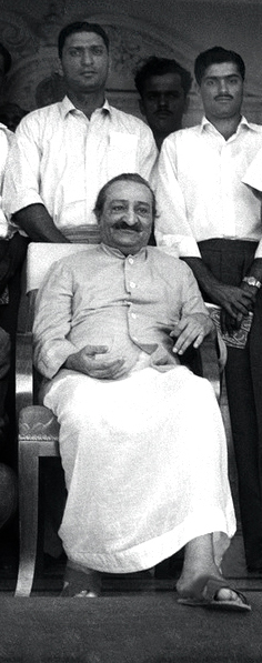 Polly ( left ) & Nari Contractor standing behind Meher Baba at Guruprasad, India.