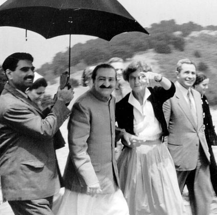 AVATAR MEHER BABA at Meher Mount on August 2, 1956, with Eruch Jessawalla holding the umbrella and Agnes Baron pointing out landmarks. (Photo from Lord Meher.)