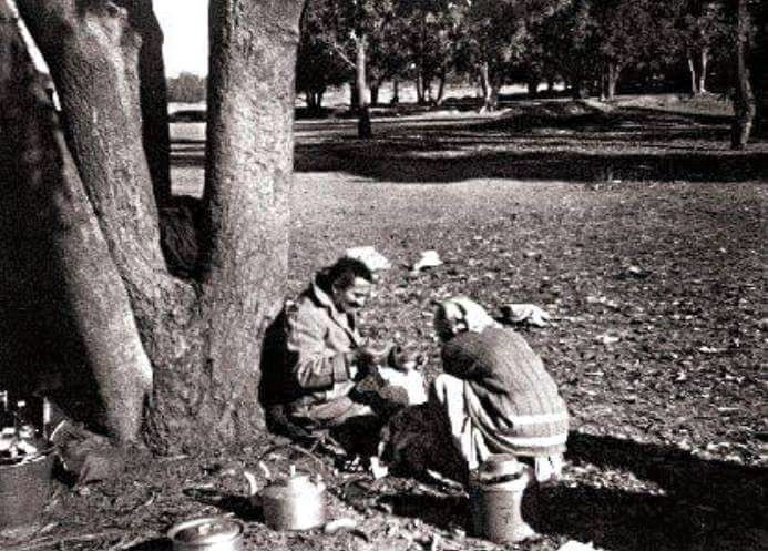 Meher Baba resting at one of the camp sites on a journey through India. Mehera Irani has prepared a meal for him.