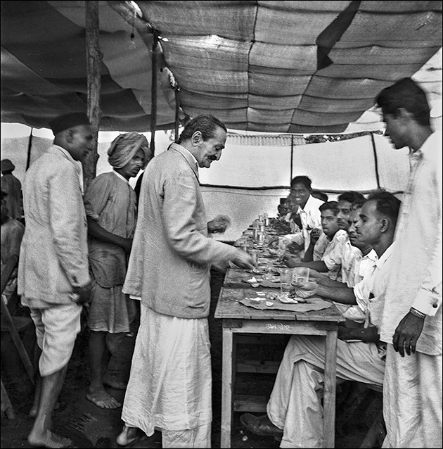 Meher Baba distributing food in the dining tent at the Final Declaration meeting, 1954