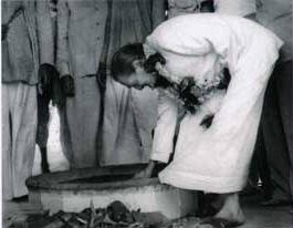 Meher Baba lighting the dhuni fire