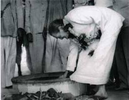 Meher Baba lighting the dhuni fire