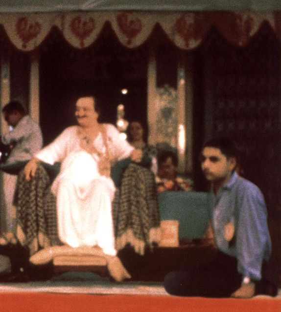 Naosherwan seated at Baba's feet at a darshan programme in India
