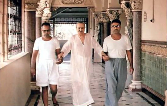 Meher Baba walking with Bhau ( left ) and Eruch Jessawala ( right ) at Guruprasad, Pune, India mid 1960s