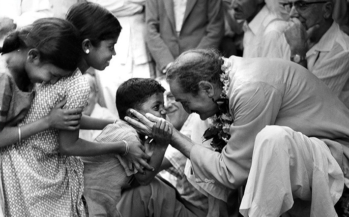 Sept.1954 - Ahmednager, India - Public darshan, Baba embracing Panday's nephew ( Suresh Panday ) with western devotees looking on