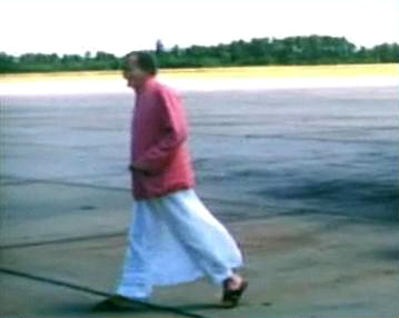 1956 : Meher Baba walking across the tarmac at Wilmington Airport, NC., after arriving from New York, on his way to Myrtle Beach, SC.  Image captured by Anthony Zois from a film by Sufism Reoriented.