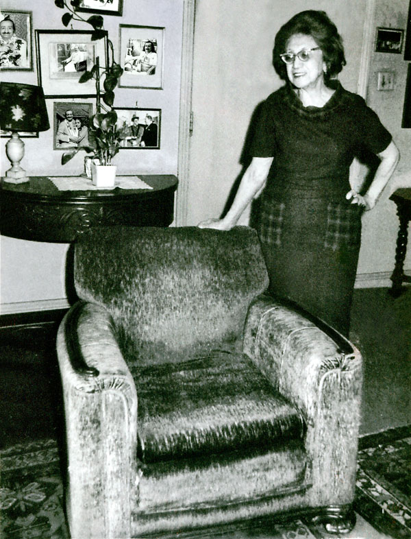 Hilda Fuchs in her Hollywood residence standing beside the chair in which Baba sat during  His visit in  1956 -Lord Meher online - p.4056