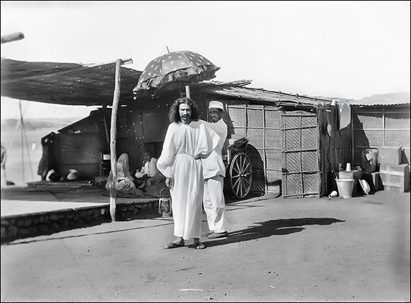 Baba is standing next to the platform, which abuts the crypt-cabin on the left, in March or April 1928 - structure behind Baba's shadow in the middle Chhota Baba and Rajaram stayed - on the right is the Sadhak Ashram.