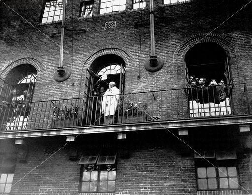 Gandhi standing at a verandar at Kingsley Hall