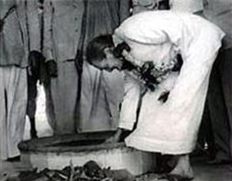 Meher Baba lighting the Dhuni