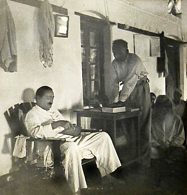 Baba seated in Lower Meherabad mandali hall giving instructions on his alphabet board with Dr Ghani standing & writing it down, at the New Life meeting - Photo taken by Padri
