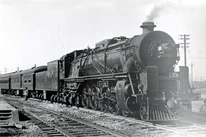 A class K7 4-8-4 locomotive towing a passenger train on the main line at Nanking, China. Sometime between the late 1930s and 1940s