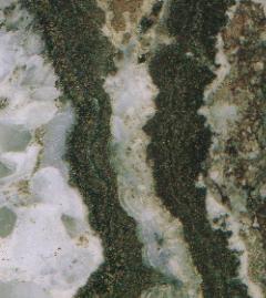 世界でも有数の品位を誇る鹿児島県菱刈鉱山の金鉱石。銀黒の石英脈から産出、鉱石の金含有量は約60g/ton。