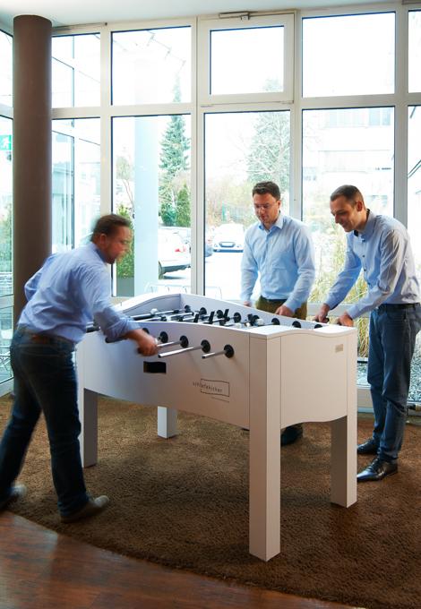 Auf diesem Bild spielen Menschen Tischfussball an einem Design-Tischkicker