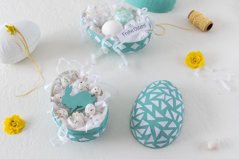 Papp-Ei als DIY-Osterüberraschung gefüllt mit weissem Ostergras und Marzipaneiern Osterhase aus Holz dekoriert mit gelben Primeln