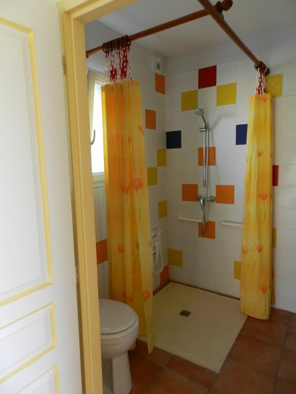 La douche avec son siège pour handicapé et le WC