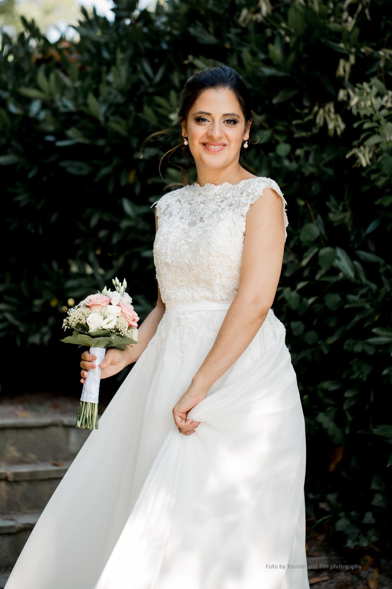 Braut mit Styling und Blumenstrauß in der Hand draußen