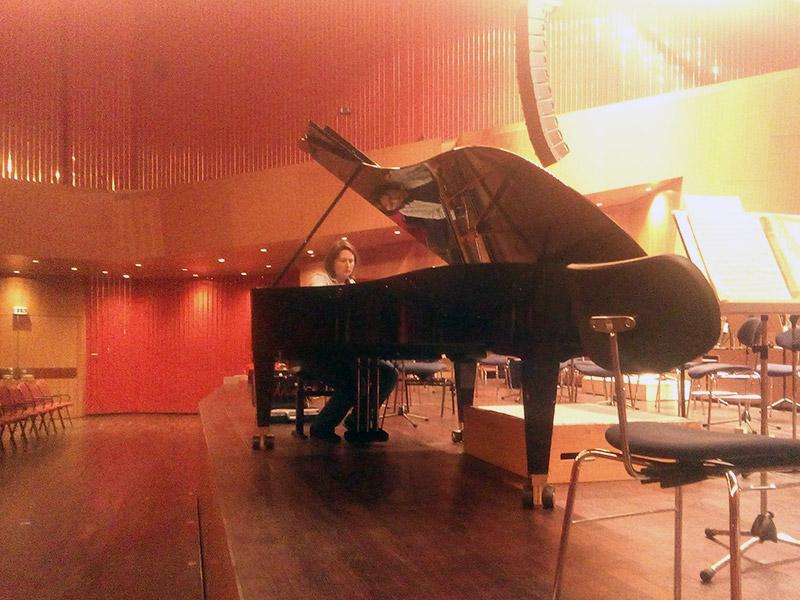 Ein schwarzer Flügel auf einer Bühne, der gerade von Anne Schmitt gestimmt wird. Im Vordergrund Stühle und Notenpulte.