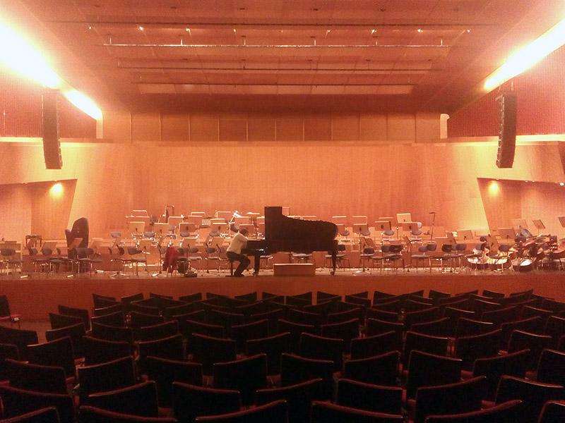 Ein schwarzer Flügel auf einer Bühne, der gerade von Anne Schmitt gestimmt wird. Im Vordergrund Stühle für das Konzert-Publikum.