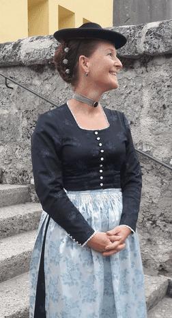 Frau in Tracht vor Kirche