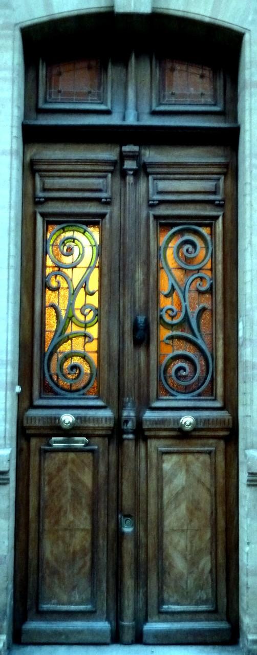 Les grilles de la porte précédente épousent étroitement le dessin du vitrail