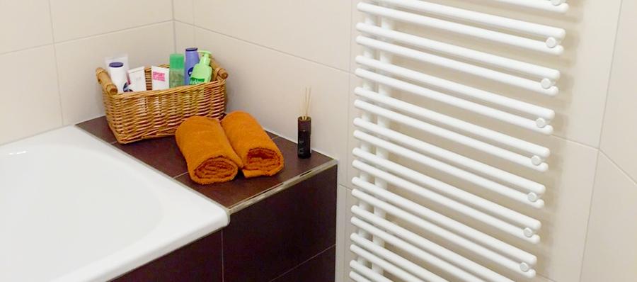 Badezimmer mit einer gefliesen Ablage im Badewannenbereich