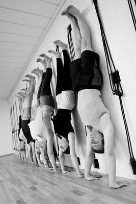 Yoga üben, Übende in Adho Mukha Vrksasana, im Handstand an der Wand
