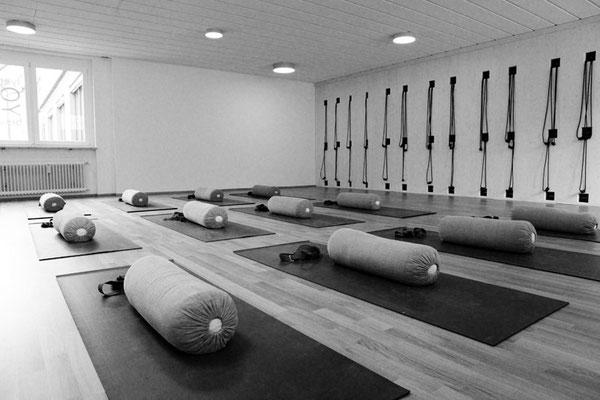 Yogaraum vorbereitet mit Übungsmatten, Polster und Gurte
