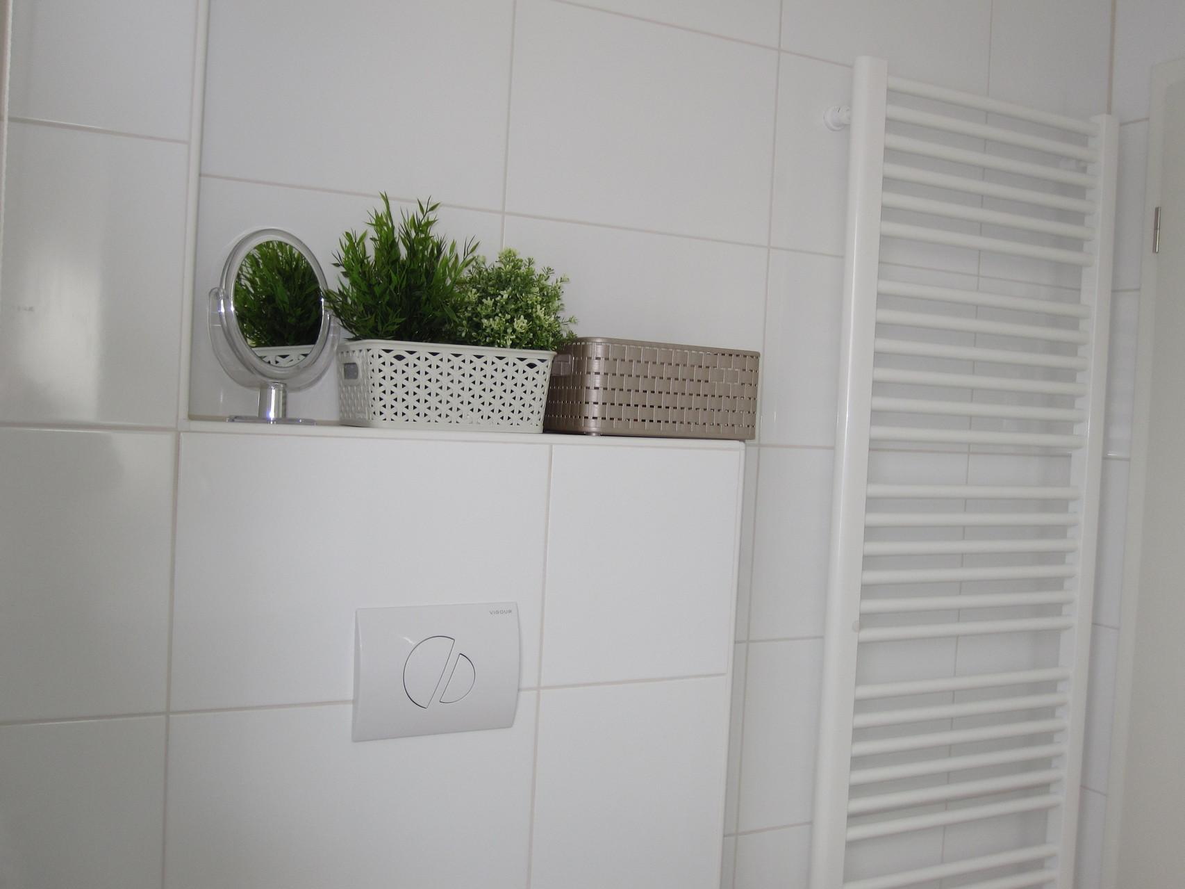 Handtuchhalterheizkörper und Kosmetikspiegel im Bad