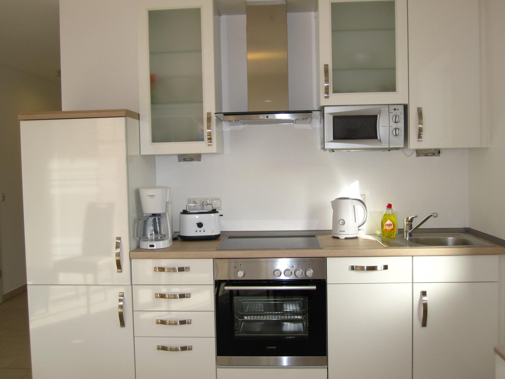 Küche mit Spülmaschine, Ceranfeld, Mikrowelle, Toaster, Kühlschrank mit Gefrierfach