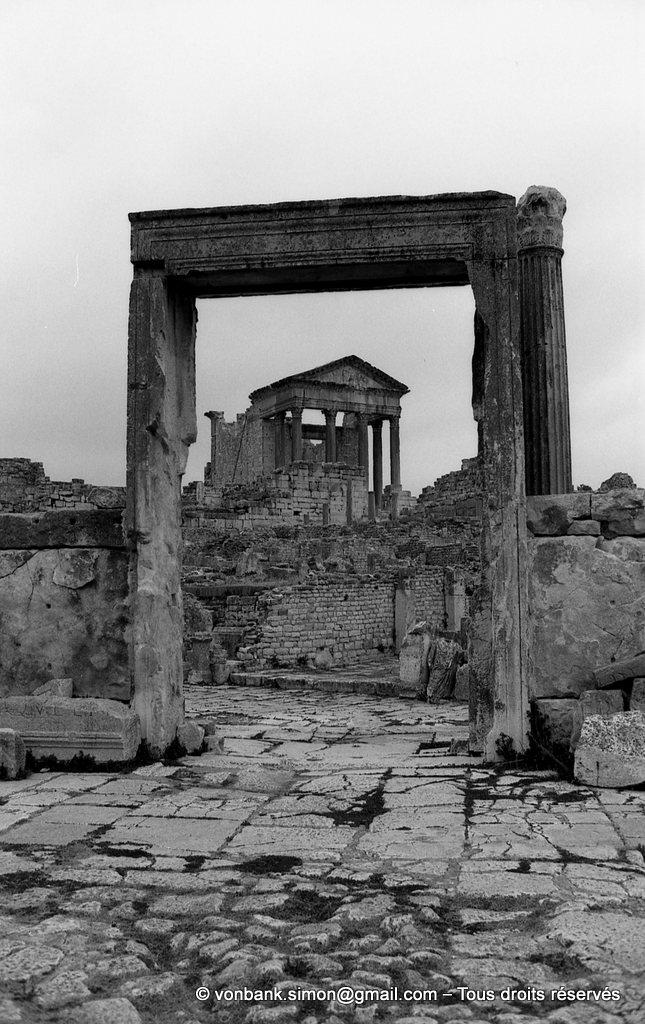[NB030-1978-24] Dougga (Thugga) : Dougga (Thugga) : Porte d'accès à l'édifice Dar El Acheb (vu de l'intérieur) - En arrière-plan, le Capitole