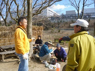 町長と談笑する山田さん、後方はポンプ修理する若松さん