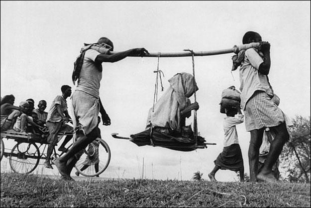 Dos hombres llevan a una mujer mayor en una camilla improvisada. (1947). Margaret Bourke-White/Getty Images
