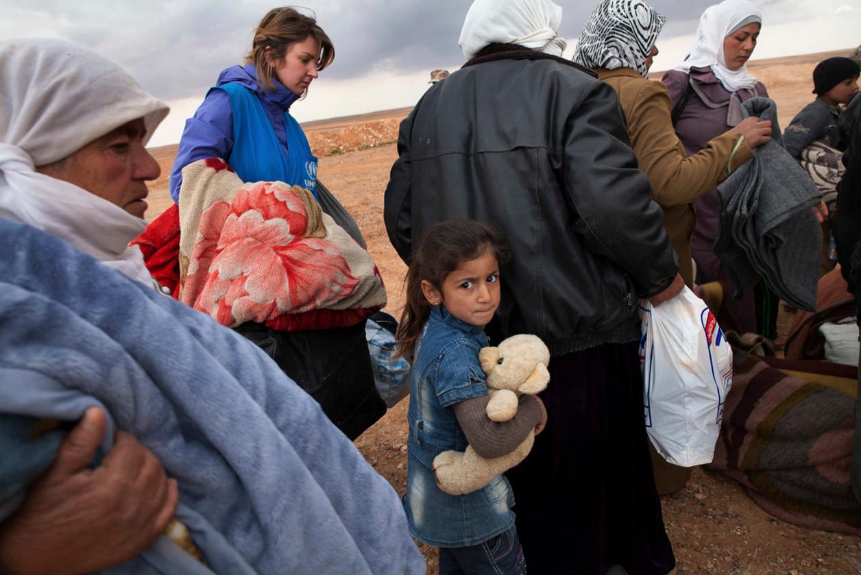 Una niña siria aprieta su oso de peluche mientras espera cruzar la frontera con Siria en Jordania (2014). Lucian Perkins