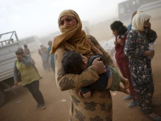 Refugiados kurdos esperan un transporte durante una tormenta de arena en lafrontera turco-siria cerca de la ciudad de Suruc (2014). Murad Sezer/Reuters