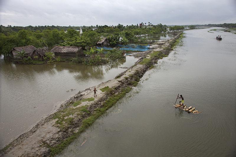 Un hombre conduce su balsa de banano a través del pueblo por las inundaciones en Satkhira (2012). Probal Rashid