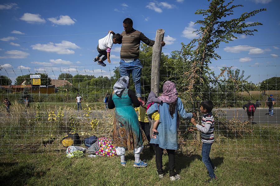 Una familia salta la valla de una autopista en el pueblo de Roszke junto a cientos de personas huyendo de la policia que queria llevarlos a un campo de refugiados. Roszke, Hungria (2015). Olmo Calvo