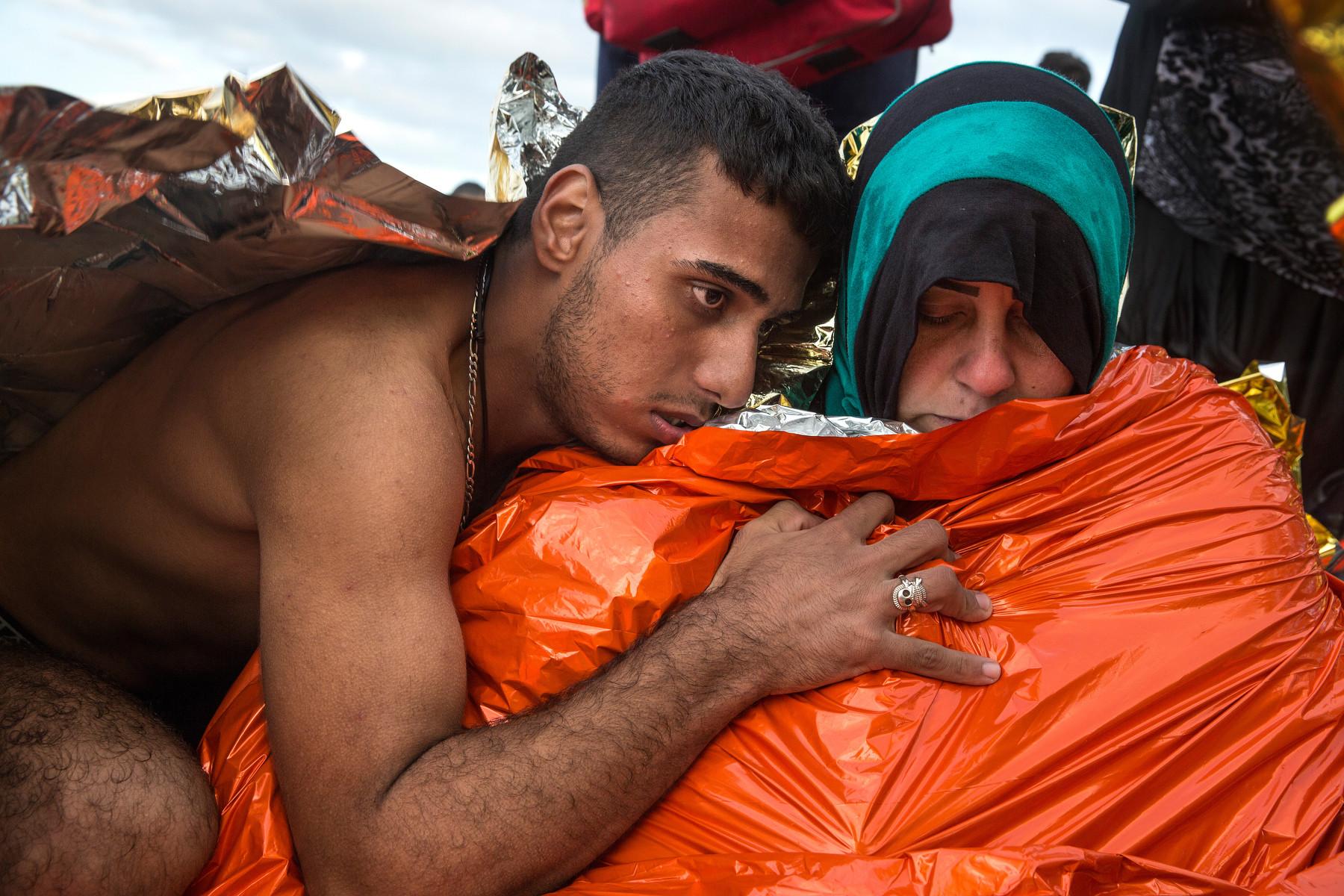 Un hombre sirio abraza a su esposa que está recibiendo atención médica por hipotermia. Lesbos (2015). Paula Bronstein/Getty Images