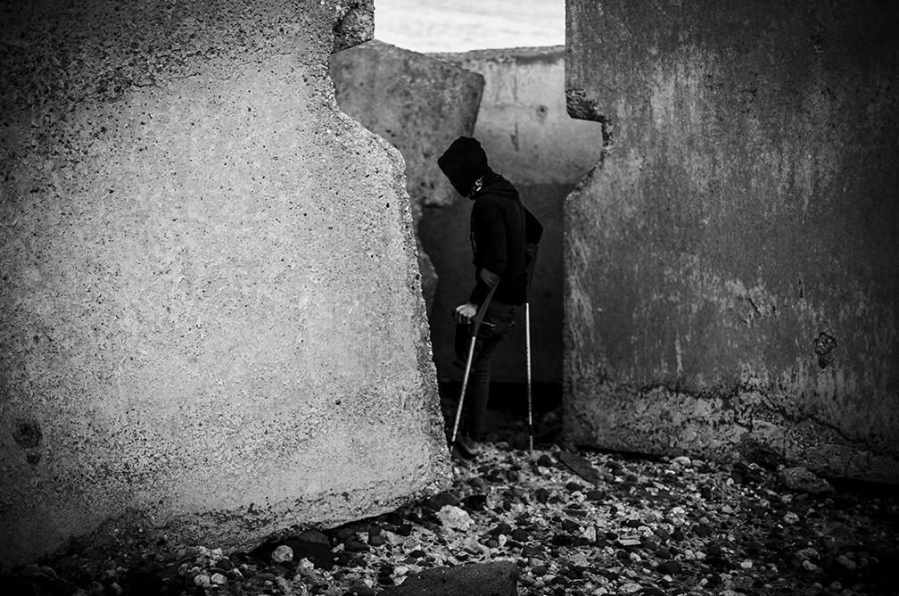 Un joven marroquí con muletas en el rompeolas del puerto de Melilla. José Colón
