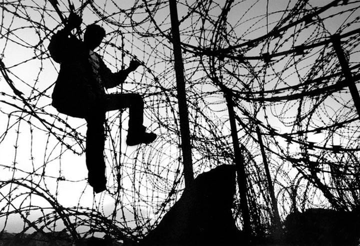 Un inmigrante marroquí trata de saltar la alambrada que separa España de Marruecos en el puerto de Ceuta. Matías Costa