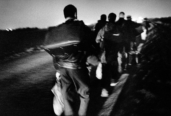 Un grupo de clandestinos camina hacia el Eurotúnel que comunica Francia con el Reino Unido, para tratar de cruzarlo escondidos en los túneles. Sangatte, Francia. Matías Costa