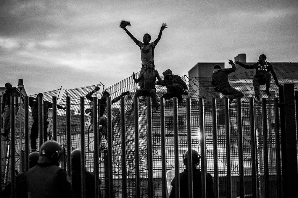 Un grupo de inmigrantes africanos intentan saltar las cercas de alambre de púas para entrar en el enclave español de Melilla de Marruecos. José Colón