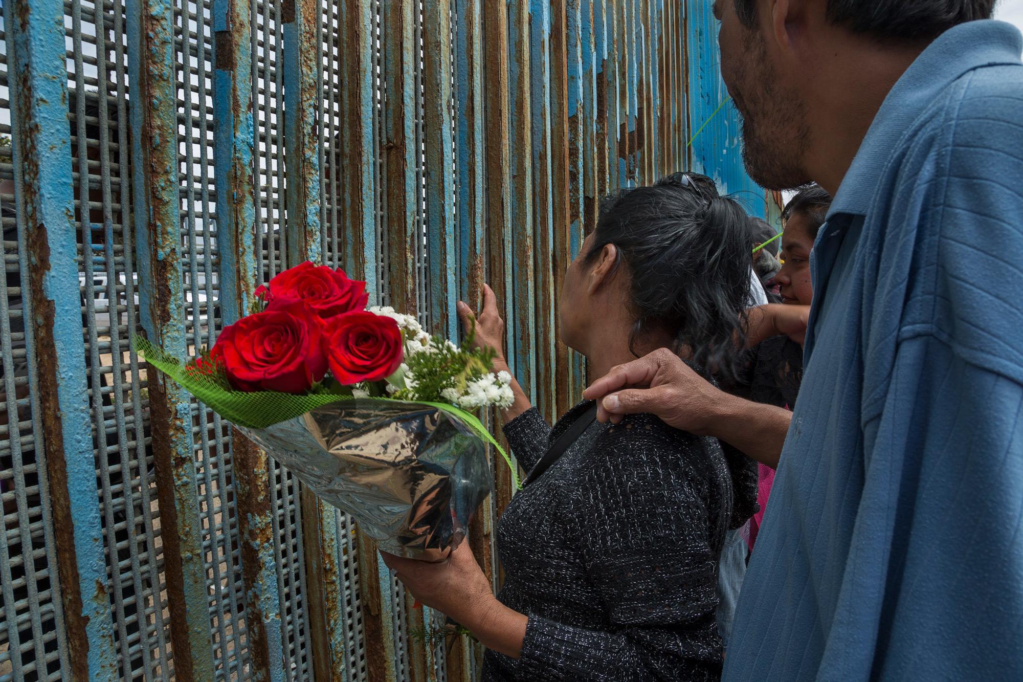 Una mujer habla con sus hijos a través del muro durante el Día de la Madre