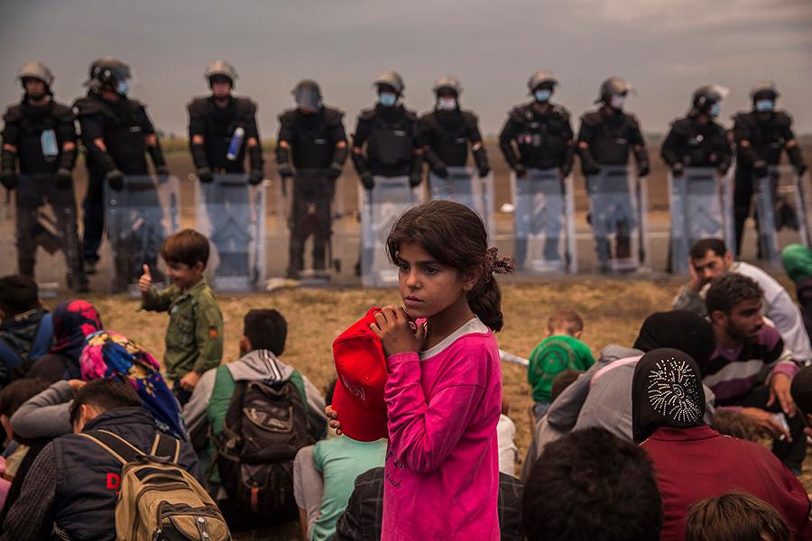 Una niña espera a ser trasladada a un campo de refugiados,  junto a cientos de personas en el punto de recepción de Roszke, fronterizo con Serbia. Roszke, Hungría (2015). Olmo Calvo