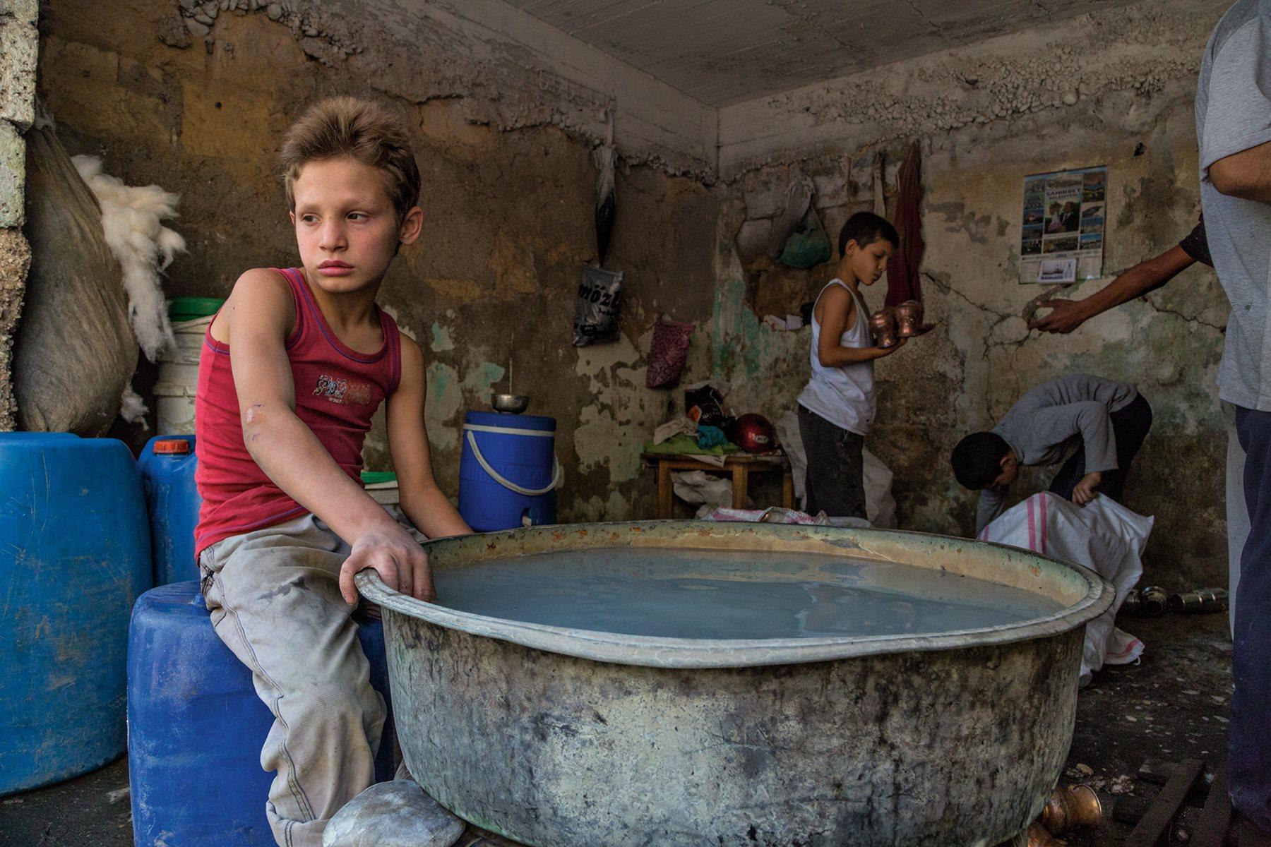 En el casco histórico de Gaziantep, Adnan, de 11 años, lava sin guantes teteras y tazas de cobre recién fabricadas para eliminar las sustancias químicas. Como muchos niños refugiados de esta ciudad, trabaja ilegalmente para ayudar a su familia (2015). Joh