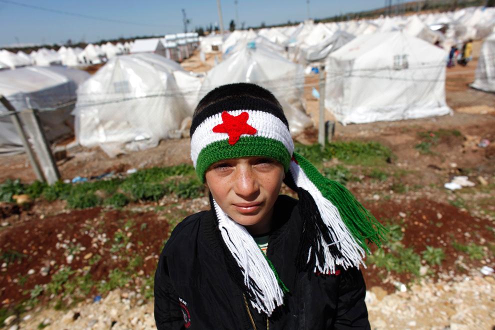 Mohammad. Niño refugiado sirio que lleva una bufanda con los colores de la bandera de la independencia de Siria. Se encuentra fuera del campo de refugiados de Reyhanli en Hatay, Turquía (2012). Murad Sezer/Reuters